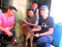 World Vets disaster response member, Dr. Helle Hydeskov, sits with a family in Guiyan, East Samar, after treating a skin infection in their dog